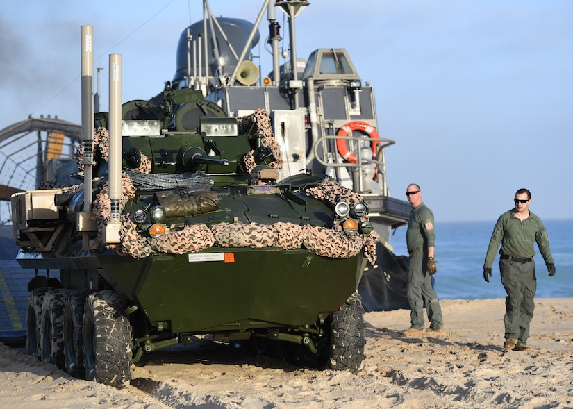 Marines unload vehicles from a landing craft.