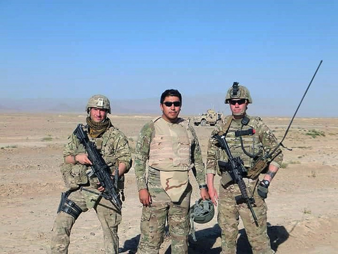 An Afghan interpreter stands with two soldiers in Afghanistan.