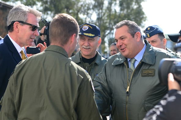 Lt. Col. Jeremy Renken, 492nd Fighter Squadron commander, shakes hands with Greek Minister of Defence Panos Kammenos during an INIOHOS 18 media event at Andravida Air Base, Greece, March 20, 2018. INIOHOS 18 is a Hellenic Air Force-led, large force flying exercise focused on strengthening partnerships and interoperability. (U.S. Air Force photo/1st Lt. Elias Small)