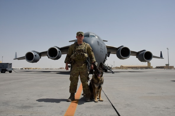 Staff Sgt. Steven Watkins and Military Working Dog, Onyx, pose for a photo in front of a KC-135 Stratotanker during a deployment. While deployed, the pair worked with an Explosive Ordnance Disposal uni and a Navy Seals unit.