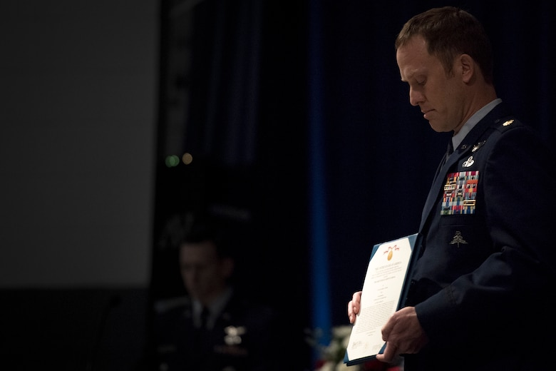 Maj. Jason Egger, 38th Rescue Squadron commander, presents a Meritorious Service Medal citation during a memorial service in honor of Capt. Mark Weber, March 21, 2018, at Moody Air Force Base, Ga. Weber, a 38th RQS combat rescue officer and Texas native, was killed in an HH-60G Pave Hawk crash in Anbar Province, Iraq, March 15. During the ceremony, Weber was posthumously awarded a Meritorious Service Medal and the Air Force Commendation Medal. (U.S. Air Force photo by Staff Sgt. Ryan Callaghan)