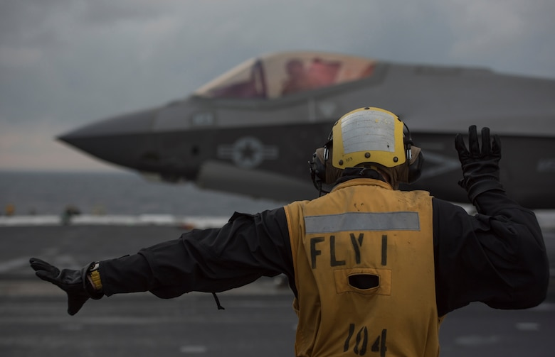 U.S. Navy Petty Officer First Class Antonio Rodriguez, Nimitz-Class aircraft carrier USS Abraham Lincoln (CVN-72) aviation boatswain's mate, directs an F-35C Lightning II assigned to Strike Fighter Squadron (VFA) 101 March 16, 2018, in the Altantic Ocean. (U.S. Air Force photo by Staff Sgt. Peter Thompson/Released)