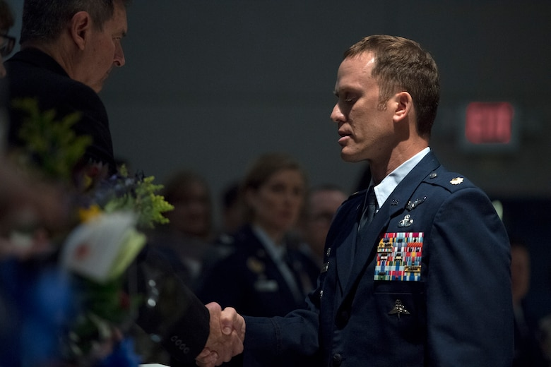 Maj. Jason Egger, 38th Rescue Squadron commander, shakes hands with Ron Weber, father of Capt. Mark Weber, during a memorial, March 21, 2018, at Moody Air Force Base, Ga. Mark, a 38th RQS combat rescue officer and Texas native, was killed in an HH-60G Pave Hawk crash in Anbar Province, Iraq, March 15. During the ceremony, Mark was posthumously awarded a Meritorious Service Medal and the Air Force Commendation Medal. (U.S. Air Force photo by Staff Sgt. Ryan Callaghan)