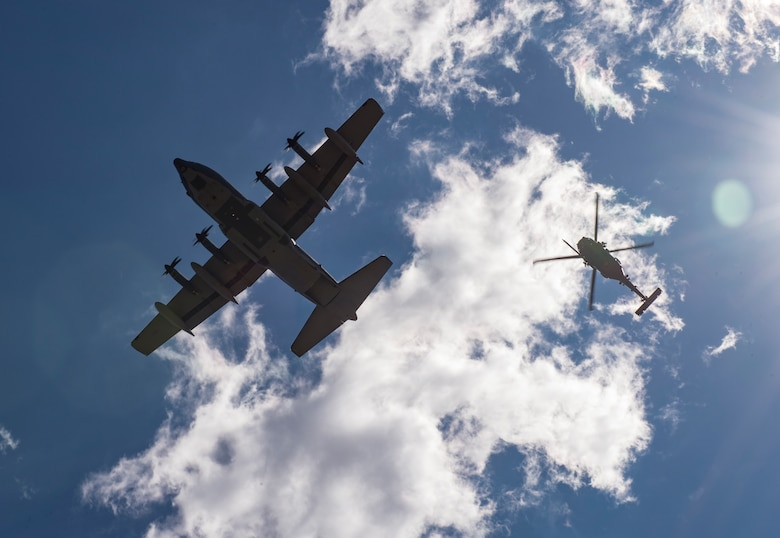 An HC-130J Combat King II and an HH-60G Pave Hawk fly over a formation of Airmen following a memorial service in honor of Capt. Mark Weber, March 21, 2018, at Moody Air Force Base, Ga. Weber, a 38th Rescue Squadron combat rescue officer and Texas native, was killed in an HH-60G Pave Hawk crash in Anbar Province, Iraq, March 15. During the ceremony, Weber was posthumously awarded a Meritorious Service Medal and the Air Force Commendation Medal. (U.S. Air Force photo by Andrea Jenkins)