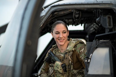 Helicopter pilot poses sitting at the door of her aircraft.