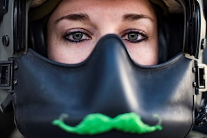 Pilot wearing a green moustache on her helmet mask poses in her aircraft.