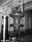 June 25, 1954 - Workers install hydroelectric turbine runner number 5 at McNary Lock and Dam, near Umatilla, Oregon.