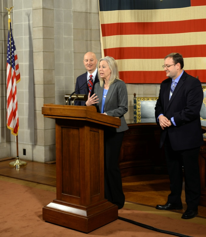 Shannon Manion, a certified teacher and veteran school administrator as well as the spouse of Col. Michael Manion, 55th Wing commander, addresses the media as Nebraska Gov. Pete Ricketts and Matt Blomstedt, commissioner of the Nebraska Department of Education, look on at the Nebraska State Capitol in Lincoln, Nebraska on March 19, 2018. According to the governor, manion was instrumental in changing Rule 21 which regulates state teaching licenses and will make it easier for military spouses to teach immediately if they have recently arrived from out of state.