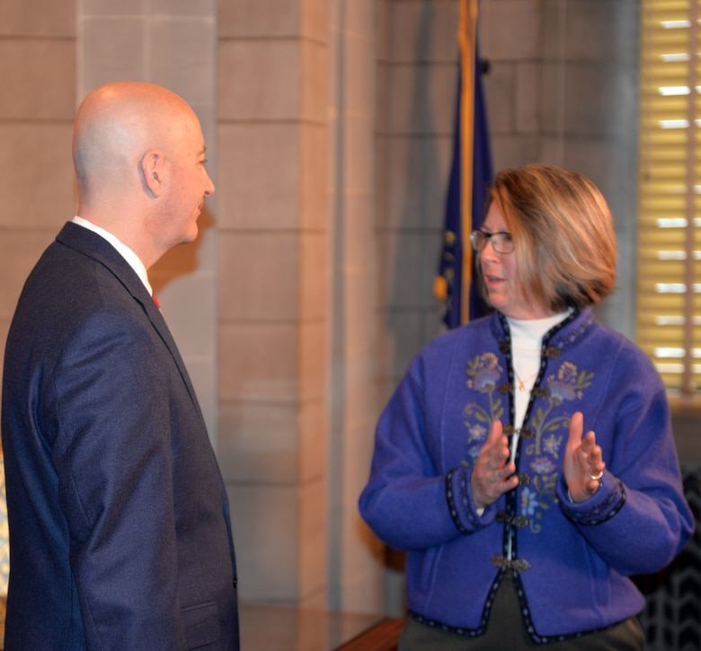 Julie Copley, spouse of Rear Adm. Curt Copley, U.S. Strategic Command (USSTRATCOM) Navy Element Commander and Director of Intelligence, discusses issues and challenges facing military spouses with Nebraska Gov. Pete Ricketts March 19, 2018, at the Nebraska State Capitol in Lincoln, Nebraska. Copley was on-hand, along with other Offutt-based military spouses, to witness the governor sign a rule change which will make it easier for military spouses to teach immediately if they have recently arrived from out of state.