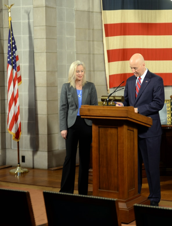 Nebraska Gov. Pete Ricketts signs a change to Rule 21, which regulates state teaching licenses, as Shannon Manion, a certified teacher and veteran school administrator as well as the spouse of Col. Michael Manion, 55th Wing commander, looks on at the Nebraska State Capitol Building in Lincoln, nebraska on March 19, 2018. Manion, along with other Offutt-based military spouses, were invited to witness the governor sign the rule change will make it easier for military spouses to teach immediately if they have recently arrived from out of state.