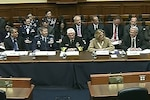 Defense Department officials sit behind a long table.