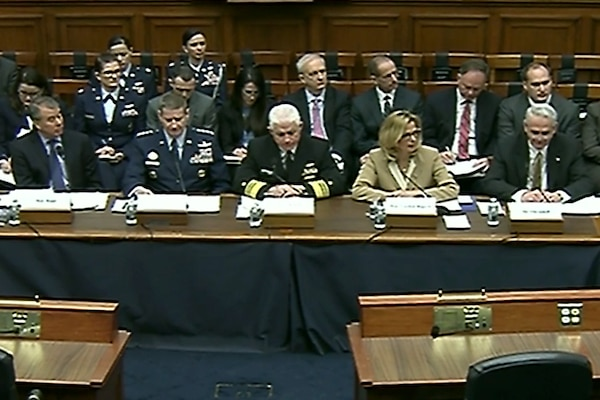 A row of civilians and military officers sit behind a desk.