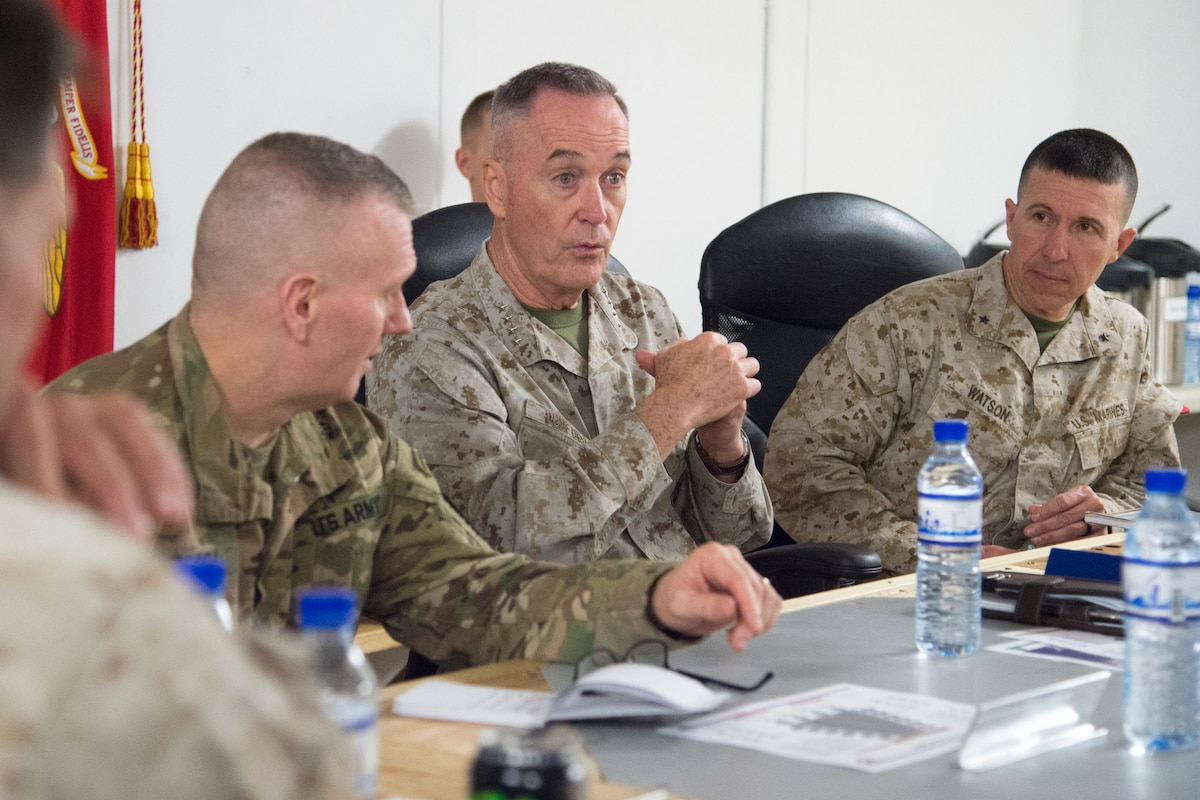 Marine Corps Gen. Joe Dunford speaks at a table as other service members listen.