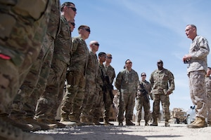 Marine Corps Gen. Joe Dunford talks to a group of soldiers standing outside.