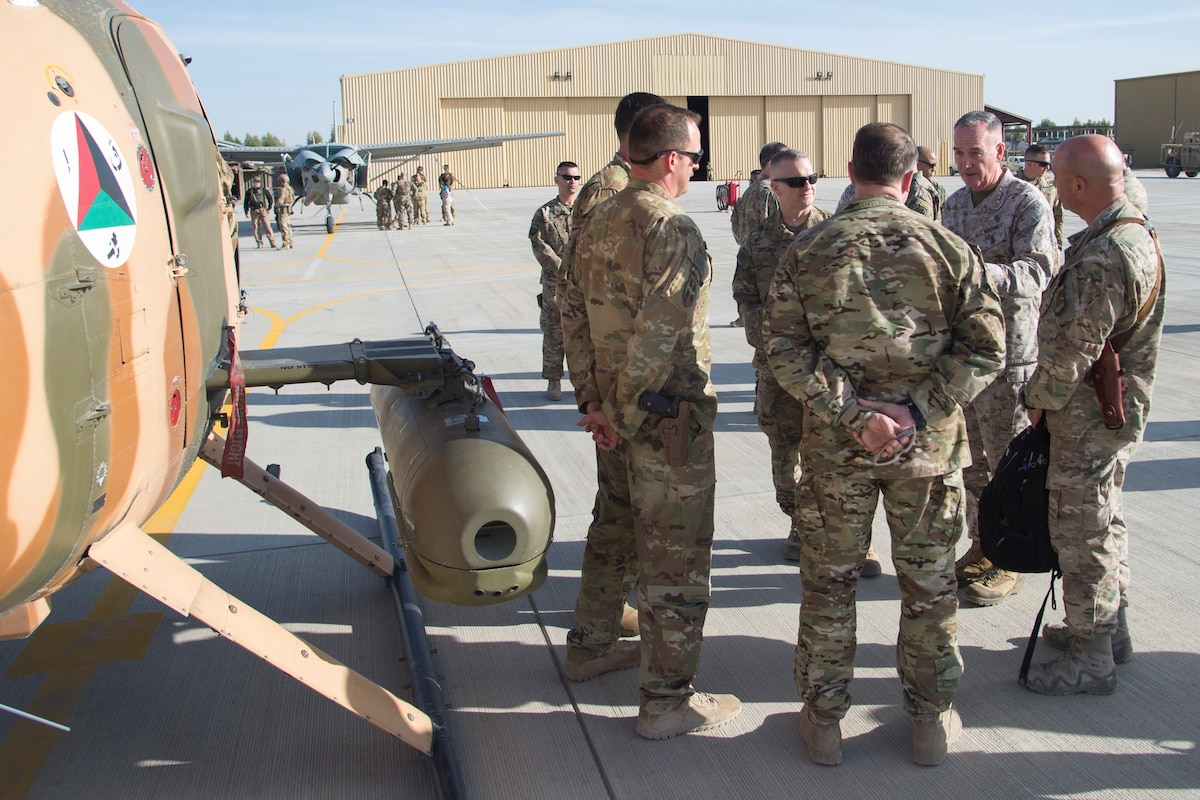 Marine Corps Gen. Joe Dunford speaks to soldiers and airmen standing near an aircraft on a flightline.