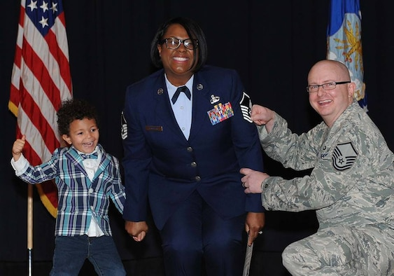 Master Sgt. Ieaka Olmstead, 22nd Operations Support Squadron host aviation resource management superintendent, has her master sergeant stripes tacked on by her husband and son.