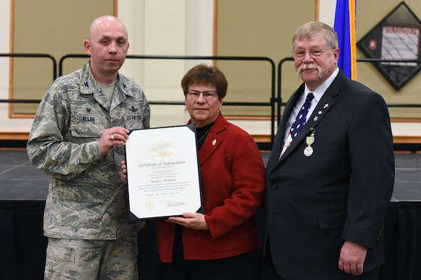 180228-F-UQ541-0657 Col. Ronald Allen, 341st Missile Wing commander, presents an award to and poses with Peter Woelkers Sr., 341st Missile Wing Weapons Safety Office chief of weapons safety/nuclear surety officer, and spouse Monica Woelkers, Feb. 28, 2018, at Malmstrom Air Force Base, Mont., during Peter's retirement ceremony. Woelkers retired after a civilian career at Malmstrom that began in 1998. (U.S. Air Force photo by Kiersten McCutchan)