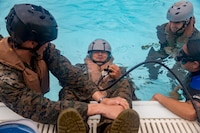 U.S. Marine Lance Cpl. Robert Stotts holds his breath to practice using the air tank during underwater egress training (UET) aboard Camp Hansen, Okinawa, Japan, Mar. 21, 2018. UET prepares Marines to escape a helicopter in the event of a mishap and lands in the water.  Stotts, a Colorado Springs, Colorado native, is a mortar man with 3rd Battalion, 3rd Marine Regiment, 3rd Marine Division. The Hawaii-based unit is currently forward-deployed to Okinawa, Japan, as part of the unit deployment program. (U.S. Marine Corps photo by Sgt. Ricky Gomez)