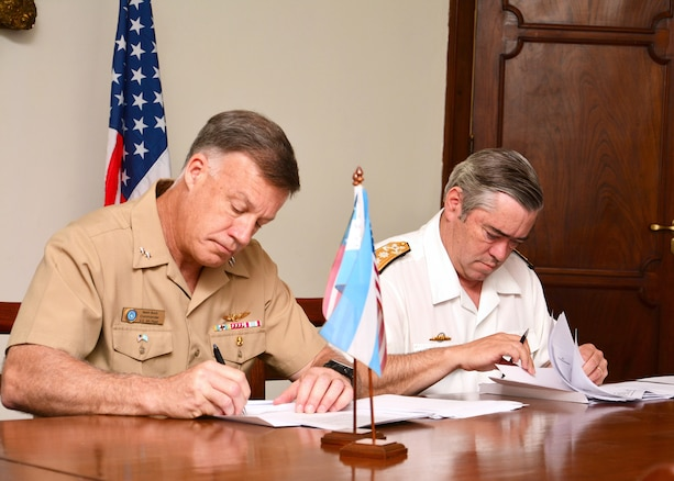 Military leaders sign documents.