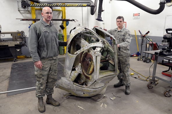Master Sgt. Garth Shannon and Staff Sgt. Robert Wheeler, 388th Maintenance Squadron, pose beside a B-24 gun turret at Hill Air Force Base, Utah, Feb. 28, 2018. Maintenance shops from the squadron are restoring the turret for the Hill Aerospace Museum. (U.S. Air Force photo by Todd Cromar)