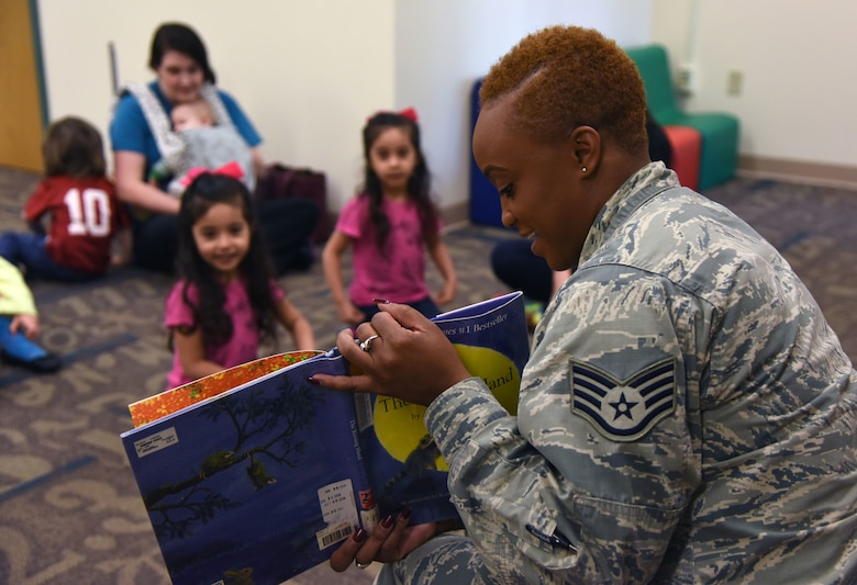 """U.S. Air Force Staff Sgt. Zsana Wrice, 81st Medical Group medical technician, reads """"The Kissing Hand"""" by Audrey Penn to Keesler children and their mothers during a story time session at the McBride Commons March 21, 2018, on Keesler Air Force Base, Mississippi. The event was held in recognition of Women's History Month. A luncheon will also be held to remember women's history March 27 at the Bay Breeze Event Center. (U.S. Air Force photo by Kemberly Groue)"""