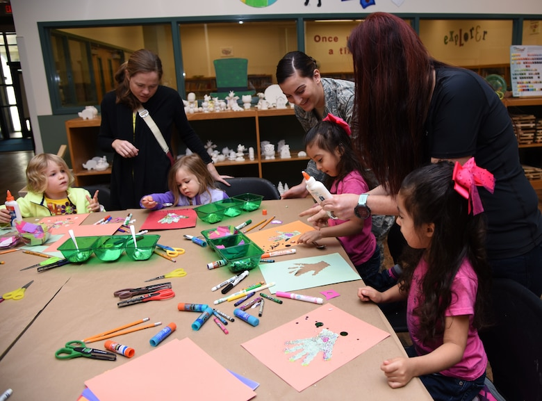 Keesler children and their mothers decorate a hand cut-out during an arts and crafts session at the McBride Commons March 21, 2018, on Keesler Air Force Base, Mississippi. Keesler children and their mothers attended the event which was held in recognition of Women's History Month. A luncheon will also be held to remember women's history March 27 at the Bay Breeze Event Center. (U.S. Air Force photo by Kemberly Groue)
