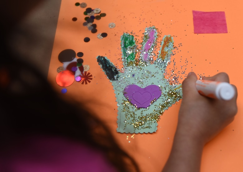 Faith Palacios, daughter of U.S. Army Sergeant 1st Class Jesus Palacios, Headquarters U.S. Army Student Detachment petroleum laboratory technician, Fort Jackson, South Carolina, decorates a hand cut-out during an arts and crafts session at the McBride Commons March 21, 2018, on Keesler Air Force Base, Mississippi. Keesler children and their mothers attended the event which was held in recognition of Women's History Month. A luncheon will also be held to remember women's history March 27 at the Bay Breeze Event Center. (U.S. Air Force photo by Kemberly Groue)