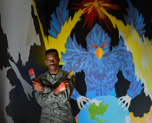 Staff Sgt. Alexander Buchanan, a 28th Operations Support Squadron aviation resource manager, stands next to an unfinished mural inside the 28th Operations Group building at Ellsworth Air Force Base, S.D., March 8, 2018. An Airman and an artist, Buchanan has spent three months designing and creating this painting outside the host aviation resource management office where he works (U.S. Air Force photo by Senior Airman Randahl J. Jenson)