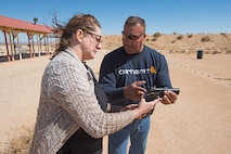 "Cynthia Poole, 412th Test Management Group honorary commander, gets a lesson on firing a hand gun from Francis ""Len"" Paris, 412th Civil Engineer Group and Rod and Gun Club member March 16. (U.S. Air Force photo by Joseph Pol Sebastian Gocong)"