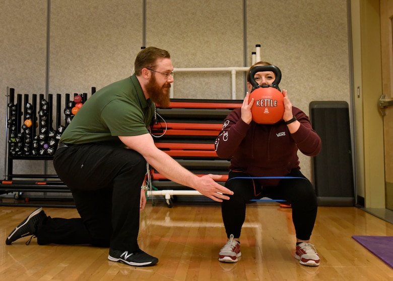 Justin Clifford, 92nd Medical Operations Squadron physical therapist, assists Staff Sgt. Jamie Skrainka, 92nd Maintenance Squadron Human Performance Cell patient, with a weighted squat at Fairchild Air Force Base, Washington, Feb. 21, 2018. Clifford is a part of a multi-disciplinary team in the HPC program that focuses on transitioning Airmen from being non-deployable to deployable, by helping them gain the strength and endurance required for success. (U.S. Air Force photo/Airman 1st Class Jesenia Landaverde)