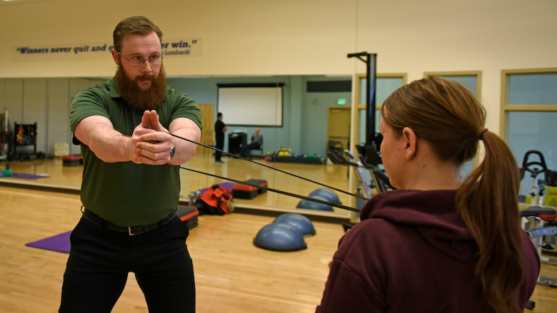 Justin Clifford, 92nd Medical Operations Squadron physical therapist, demonstrates resistance band training to Staff Sgt. Jamie Skrainka, 92nd Maintenance Squadron Human Performance Cell patient, at Fairchild Air Force Base, Washington, Feb. 26, 2018. Starting in October, all military members who have been non-deployable for more than 12 consecutive months, for any reason, will be processed for administrative separation. The HPC program's objective is to reduce the number of non-deployable service members and improve personnel readiness across the force. (U.S. Air Force photo/Airman 1st Class Jesenia Landaverde)