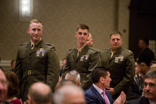 Marines with Marine Wing Support Squadron 473 stand to show they were the winners of Marine Corps Logistics Organization/Team of the Year for a large unit award before the opening ceremony of the Marine Corps Association and Foundation's 14th annual Ground Logistics Awards Dinner at the Crystal Gateway Marriott, Arlington, Virginia, March 22, 2018. MWSS-473 was given the award in part for their hurricane relief efforts and their aide efforts when Marine Aerial Refueler Transport Squadron 452 crashed in Mississippi. (U.S. Marine Corps photo by Cpl. Dallas Johnson)