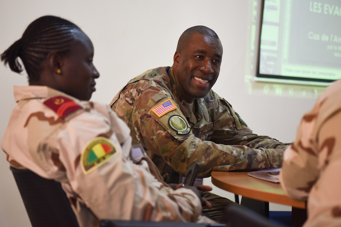 Capt. Malick Traore, 818th Mobility Support Advisory Squadron aeromedical evacuation project manager, discusses principles of altitude physiology and stresses of flight with a Malian chief of medical operation during African Partnership Flight Senegal, March 20, 2018. Partnership flights are U.S. Air Forces Africa's premier security cooperation program with African partner nations to improve professional military aviation knowledge and skills. (U.S. Air Force photo by Capt. Kay Magdalena Nissen)