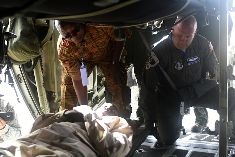 A participant of African Partnership Flight Senegal and U.S. Air Force Maj. Forrest Moodispaw, 167th Aeromedical Evacuation Squadron flight nurse, load patients onto a West Virginia Air National Guard C-130 H Hercules, assigned to the 130th Airlift Wing, at Captain Andalla Cissé Air Base, Senegal, March 22, 2018. APF brings neighboring countries together to learn practical and applicable aviation skills from U.S. Airmen. (U.S. Air Force photo by Airman 1st Class Eli Chevalier)