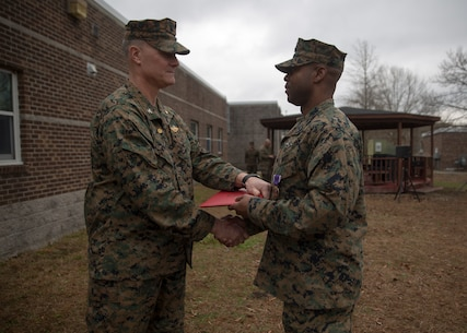 Capt. Brian Tolbert, the commanding officer of 2nd Medical Battalion, 2nd Marine Logistics Group, awards Petty Officer 2nd Class Willie Jones, a corpsman with 2nd Med. Bn., a Purple Heart during an award ceremony at Camp Lejeune N.C., Feb. 8, 2018. Jones was awarded the Purple Heart for injuries sustained from a vehicle borne improvised explosive device in Afghanistan, Sept. 6 2017. Despite his own injuries, Jones provided aid for injured service members when a VBIED detonated during a patrol