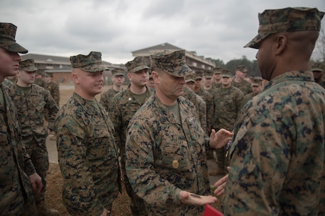Master Chief Petty Officer Russell Folley, the command master chief of 2nd Marine Division, gives Petty Officer 2nd Class Willie Jones, a corpsman with 2nd Medical Battalion, 2nd Marine Logistics Group, a coin after a Purple Heart award ceremony at Camp Lejeune N.C., Feb. 8, 2018. Jones was awarded the Purple Heart for injuries sustained from a vehicle borne improvised explosive device in Afghanistan, Sept. 6 2017. Despite his own injuries, Jones provided aid for injured service members when a VBIED detonated during a patrol. (U.S. Marine Corps photo by Cpl. Victoria Ross)