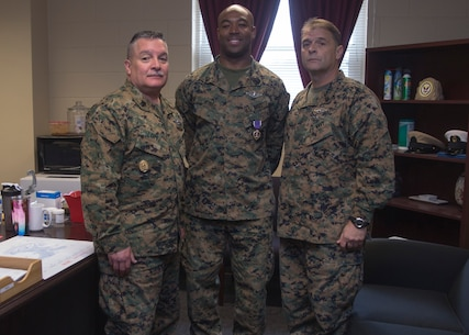 Master Chief Petty Officer Juan Lopez, left, the command master chief of 2nd Medical Battalion, 2nd Marine Logistics Group, and Master Chief Petty Officer Russell Folley, right, the command master chief of 2nd Marine Division, pose with Petty Officer 2nd Class Willie Jones, center, a corpsman with 2nd Med. Bn., for a photo at the conclusion of a Purple Heart award ceremony at Camp Lejeune N.C., Feb. 8, 2018. Jones was awarded the Purple Heart for injuries sustained from a vehicle borne improvised explosive device in Afghanistan, Sept. 6 2017. Despite his own injuries, Jones provided aid for injured service members when a VBIED detonated during a patrol. (U.S. Marine Corps photo by Cpl. Victoria Ross)