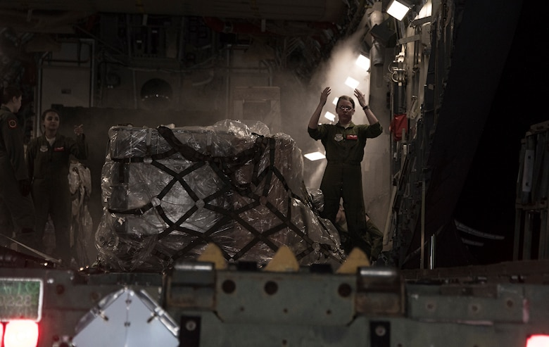 Airman 1st Class Alexia Lewis, a loadmaster assigned to the 21st Airlift Squadron marshals a tunner loader into position, March 18, 2018, at Andersen Air Force Base, Guam, during a Women's Heritage Flight. Lewis was part of an all-female C-17 Globemaster III crew that honored Women's History Month and highlighted AMC's ability to conduct rapid global mobility in today's Air Force by delivering equipment and military personnel to the Pacific Command area of responsibility. (U.S. Air Force photo by Heide Couch)