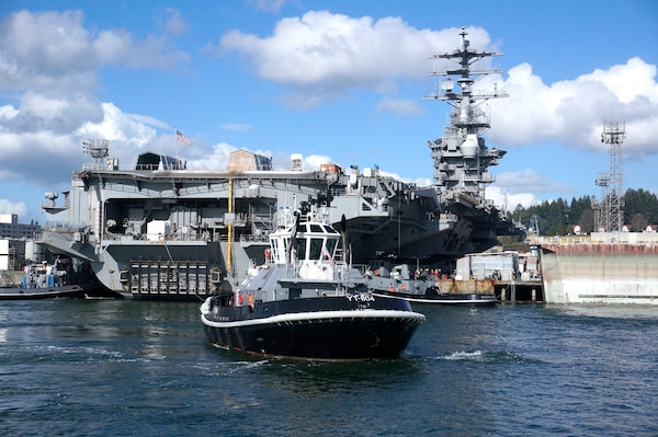 Harbor tug Defiant (YT 804) and crew wait to assist while USS Nimitz (CVN 68) is being positioned for docking at Puget Sound Naval Shipyard & Intermediate Maintenance Facility in Bremerton, Washington March 1, 2018.
