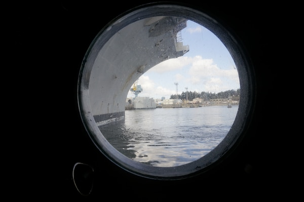 View of USS Nimitz (CVN 68) from tugboat porthole