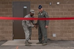 Airman Johnny Jackson, 56th Logistics Readiness Squadron Fuels Management operator, cuts the ribbon with Brig. Gen. Brook Leonard, 56th Fighter Wing commander, to open the new fuel pump house at Luke Air Force Base, Ariz., March 15, 2018. Leonard and other members of Luke's command team were present for the pump house's ribbon-cutting ceremony. (U.S. Air Force photo by Senior Airman Ridge Shan)