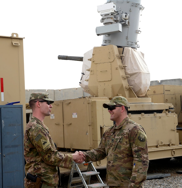 U.S. Army Capt. Eric Sylwestrak, battery commander, 2nd Battalion, 174th Air Defense Artillery Regiment, Ohio Army National Guard, shakes hands with U.S. Air Force Capt. Isaac Hoffman, project engineering officer-in-charge, 220th Engineering Installation Squadron, Ohio Air National Guard, in front of one of the Army's Counter-Rocket, Artillery, and Mortar (C-RAM) Intercept weapon systems at Kandahar Airfield, Afghanistan, March 10, 2018.