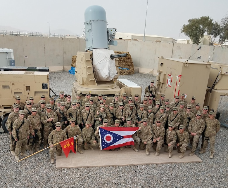 Airmen with the 220th Engineering Installation Squadron, Ohio Air National Guard, and Soldiers with the 2nd Battalion, 174th Air Defense Artillery Regiment, Ohio Army National Guard, pose for a group photo in front of one of the Army's Counter-Rocket, Artillery, and Mortar (C-RAM) Intercept weapon systems at Kandahar Airfield, Afghanistan, March 10, 2018.