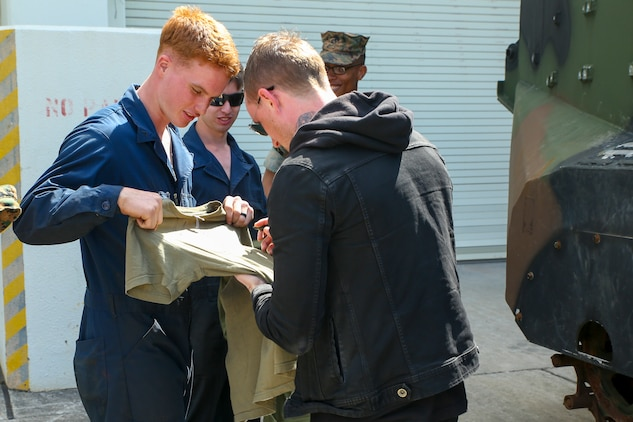 A member of rock band, Asking Alexandria, signs a Marine's skivvy shirt during a meet and greet with Marines March 23 aboard Camp Schwab, Okinawa, Japan. Band members were able to get close and learn about the different military vehicles while meeting with Marines. The band later performed for Marines and their families at the Annual Schwab Festival. (U.S. Marine photo by Pfc. Nicole Rogge)