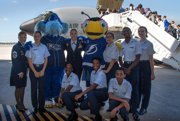 U.S. Air Force Col. April Vogel, the commander for the 6th Air Mobility Wing, pauses for a photo with students and Tampa Bay team mascots during the Science, Technology, Engineering, Arts and Math (STEAM) Day at MacDill Air Force Base, Fla., March 21, 2018.