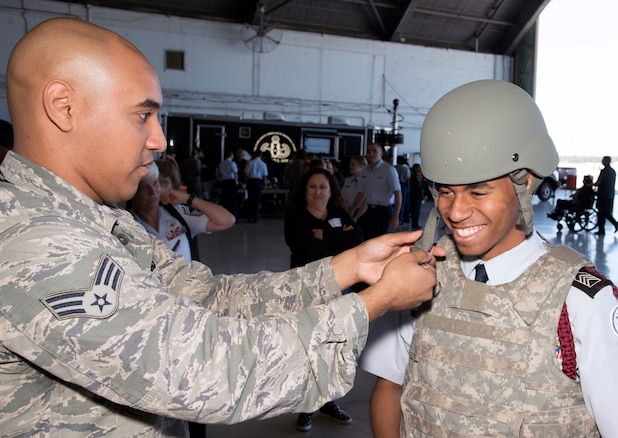 U.S. Air Force Senior Airman Christian Espada, an individual protective equipment journeyman assigned to the 6th Logistics Readiness Squadron, fits a student with an individual operator tactical vest (IOTV) and helmet during the Science, Technology, Engineering, Arts and Math (STEAM) Day at MacDill Air Force Base, Fla., March 21, 2018.
