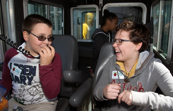 Two young students share a laugh while talking about the public address system upon a secured all-around flotation equipped (SAFE) boat during the Science, Technology, Engineering, Arts and Math (STEAM) Day at MacDill Air Force Base, Fla., March 21, 2018.