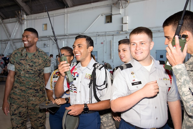 U.S. Marine Sgt. Christopher Dobard, a team chief assigned to Joint Communications Support Element, laughs with students while communicating through a multiband multi mission radio during the Science, Technology, Engineering, Arts and Math (STEAM) Day at MacDill Air Force Base, Fla., March 21, 2018.