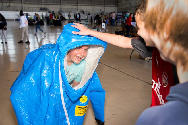 """A Florida student tries on an occupational safety health administration (OSHA) level """"A"""" suit during the Science, Technology, Engineering, Arts and Math (STEAM) Day at MacDill Air Force Base, Fla., March 21, 2018."""