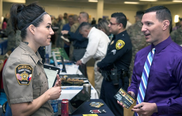 A recruiter with the Travis County Sheriff's Office talks to a visitor at the Hiring Heroes Career Fair March 21 in the Sam Houston Community Center at Joint Base San Antonio-Fort Sam Houston. At the fair, transitioning, ill, injured and wounded service members, veterans and military spouses got to talk to representatives from employers, companies and governmental agencies on career opportunities.